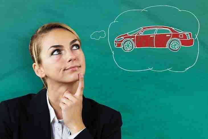 Junge Frau stellt sich ein in einer Sprechblase dargestelltes rotes Auto vor