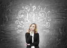 Nachdenkliche junge Frau vor einer Wandtafel mit Fragezeichen. Warum Kreditablehnung trotz positiver SCHUFA?