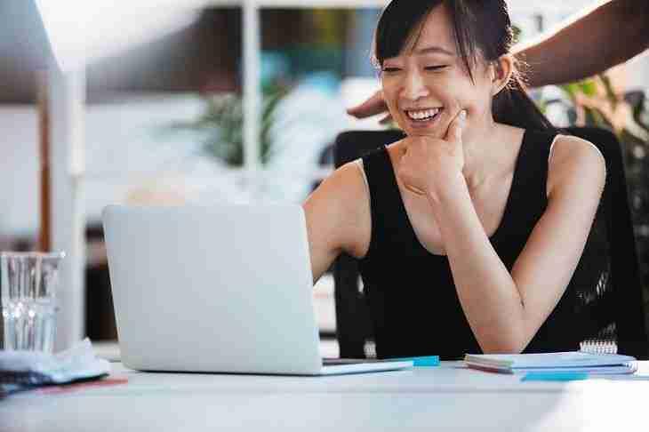 Junge Frau am Laptop beantragt online einen Kredit trotz SCHUFA