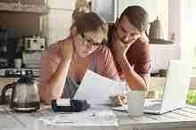 Junges Ehepaar vor einem Computer mit Darlehensunterlagen zur Vorbereitung einer Umschuldung ohne SCHUFA