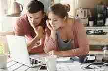 Nachdenkliches junges Ehepaar am Computer. Wo am besten Kredit beantragen?