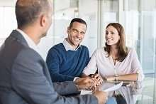 Kreditvermittler berät junges Ehepaar
