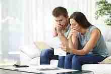 Junges Ehepaar am Computer beantragt gemeinsam Hausfrauenkredit