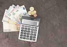Rechner mit Euroscheinen und Münzen Kleinkredit ohne Festvertrag