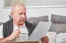 Rentner studiert eine Unterlage: Kredit für Ruheständler über 70